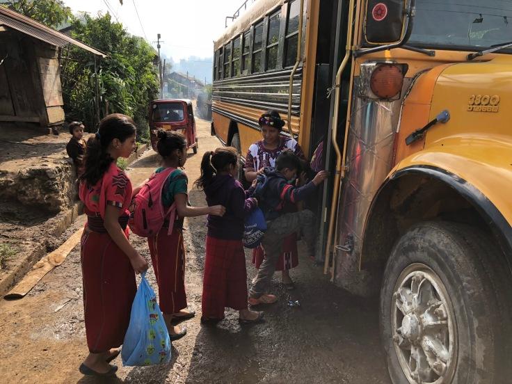 teacher watches as kids get into a schoolbus