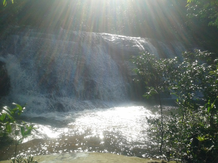 sun shining down on waterfall