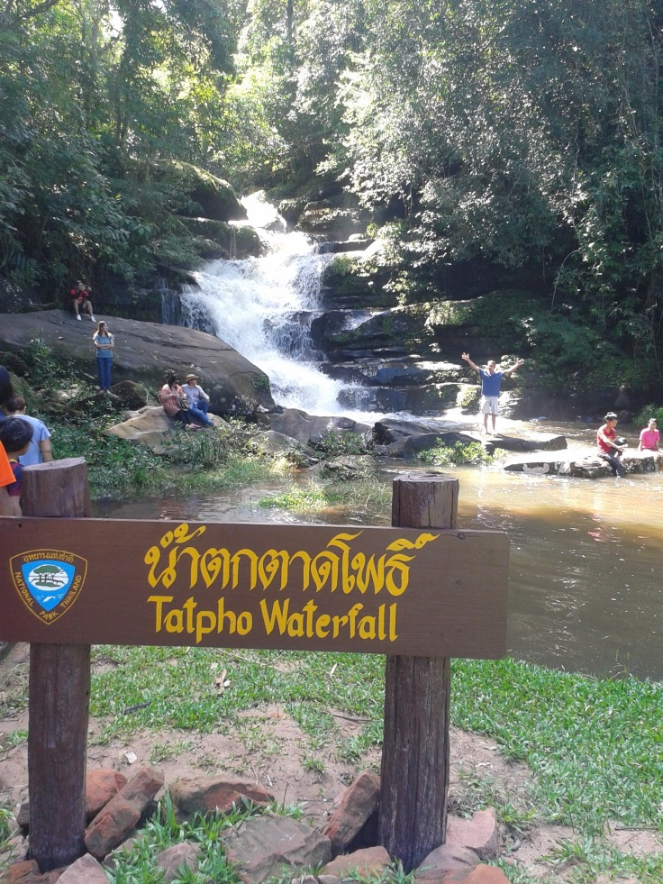 "sign in english and thai ""tatpho waterfall"" and waterfall in background"